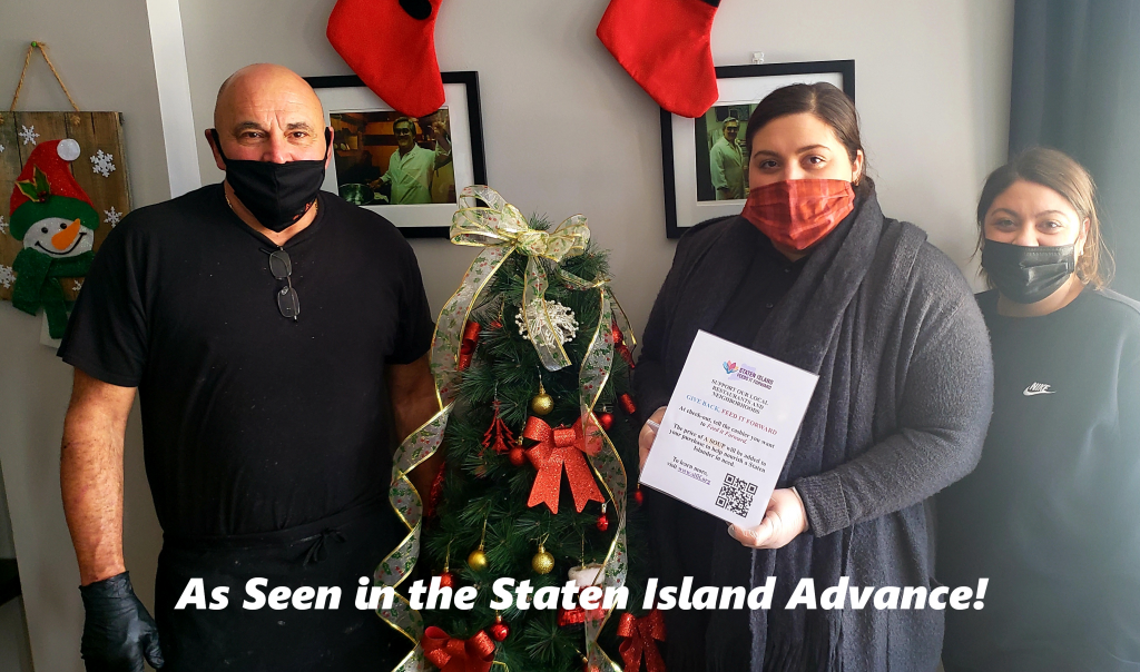 """Three people surrounding a Christmas Tree, all are masked, one on the right is holding the Staten Island Feeds It Forward Sign. Caption reads """"As seen in the Staten Island Advance!"""""""