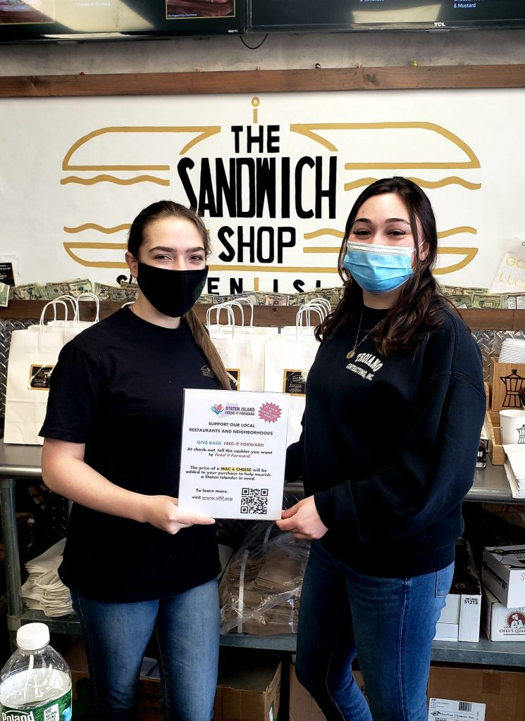 Two women with masks holding the SIFIF Sign, The Sandwich Shop sign is visible behind them.