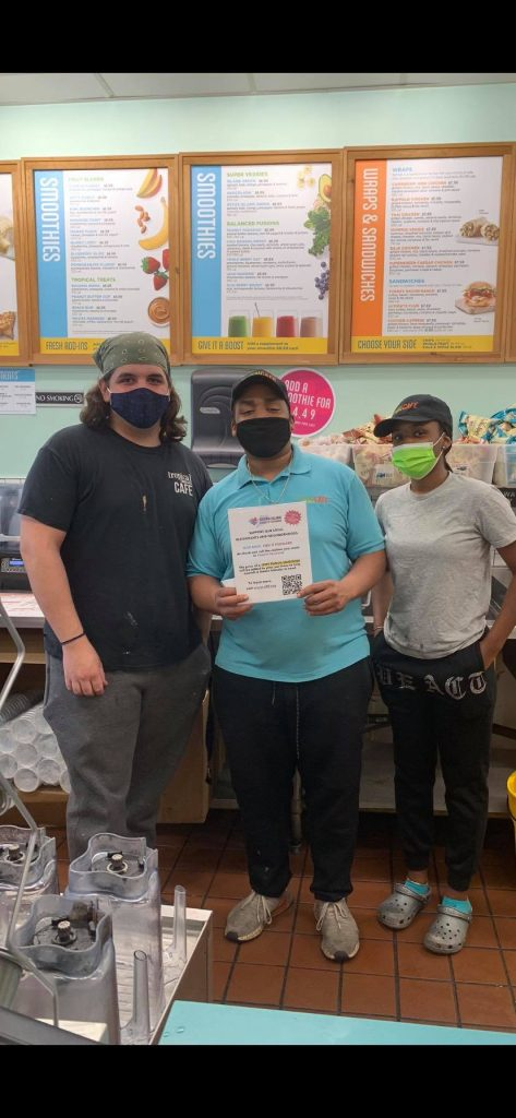 Three masked people in front of a counter, the middle person holding a Staten Island Feeds It Forward Sign. The restaurant's menus are visible in the background.