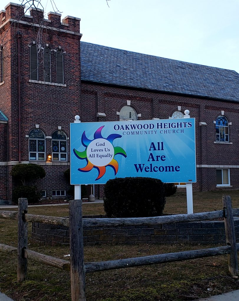 """Oakwood Heights Community Church in background with sign stating """"God Loves Us All Equally"""" and """"All Are Welcome"""""""